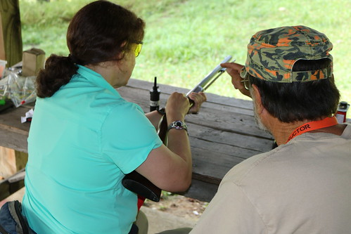 Photo of woman at an outdoor clinic learning to load a muzzeloader