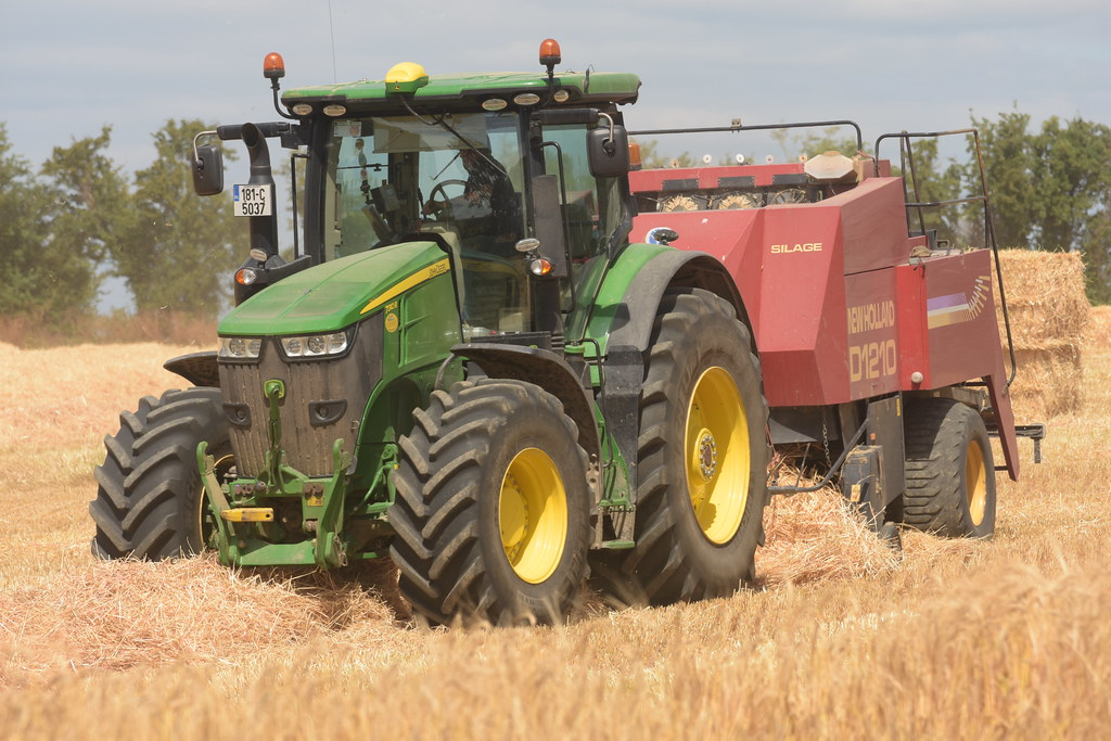 John Deere 7310R Tractor with a New Holland D1210 Square B