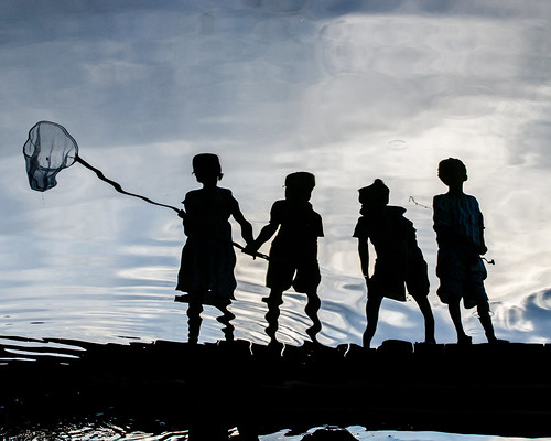 Photo of reflection of four young crabbers with a dip net