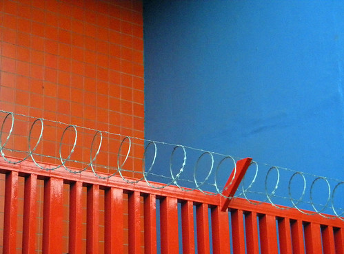 A red fence with razor wire creates a pretty picture against blue and red tiled walls in Costa Rica