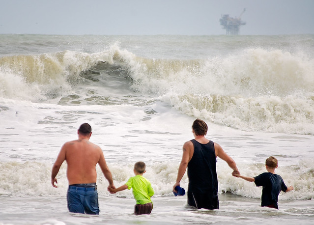 Fathers and sons play in waves as Tropical Storm Gordon approaches Dauphin Island Alabama