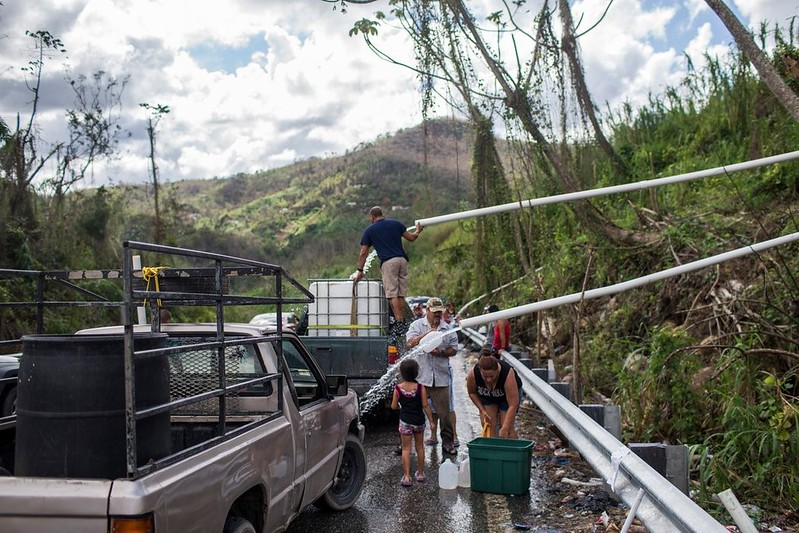 Ciudadanos llenado sus cubos en la carretera PR 10 Utuado