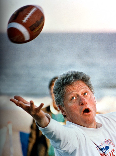 US President Bill Clinton reaches to catch a football