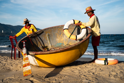 danang vietnam asia beach basket boat men coast coastguard man lifeguard sea ocean yellow orange sunset sand blue hat chair