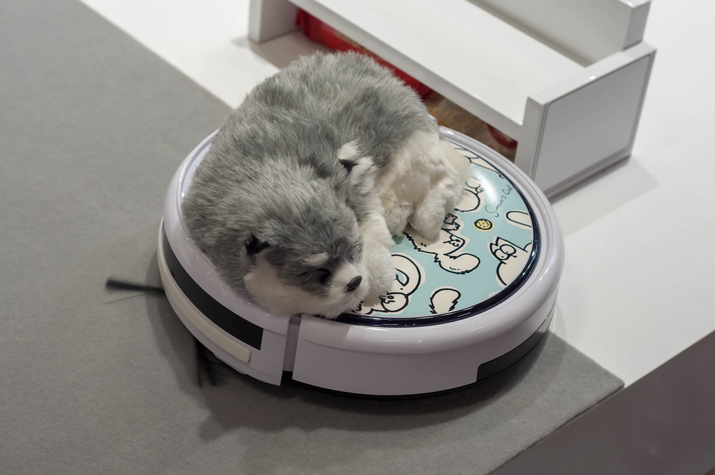 Soft toy dog on a robot vacuum cleaner with Simon's Cat ca… | Flickr