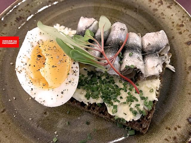 Homemade Rye Bread With Hemp Seeds, Spiced Sprat, Soft Egg, Farmhouse Butter & Herbs