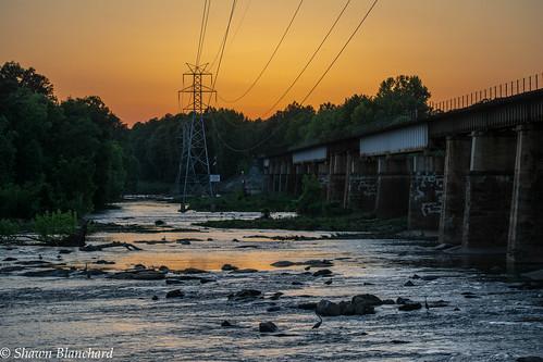 sunset water sky red orange yellow trees rocks broad river riverfront park south carolina sc columbia state capital capitol telephone lines bridge