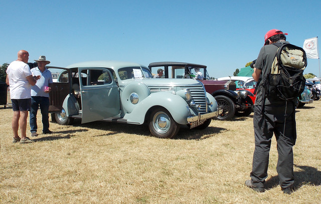 MEN STAND TALKING NEXT TO A 1938 HUDSON SEDAN AUTOMOBILE OR MOTOR CAR WHILE A MALE PHOTOGRAPHER STANDING TAKING A PHOTO AT A STEAM AND CIDER SHOW IN AN EAST LONDON BOROUGH SUBURB STREET PARK VENUE ENGLAND DSCN1523
