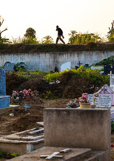Angolan man walking o the wall of an old cemetery, Benguela Province, Catumbela, Angola | by Eric Lafforgue