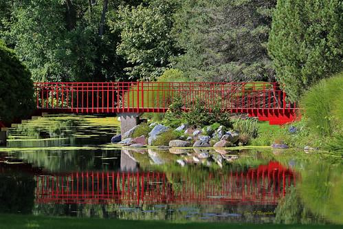 red redorange vermillion carmine bridge redbridge pedestrianbridge reflection water pond river rocks boulders landscape scenery trees peaceful serene shadows midland michigan jannagalski jannagal