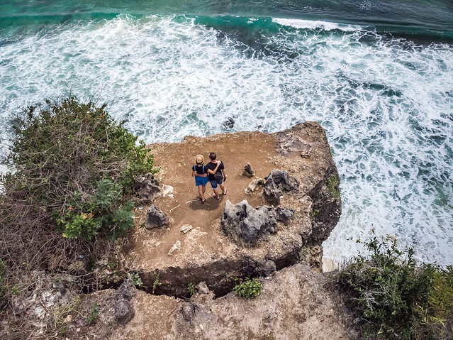 Aerial shot of couple on the cliff with ocean background.