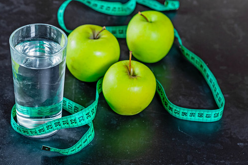 The concept of weight loss: the green apples and a glass of water with a measuring tape on black background | by wuestenigel