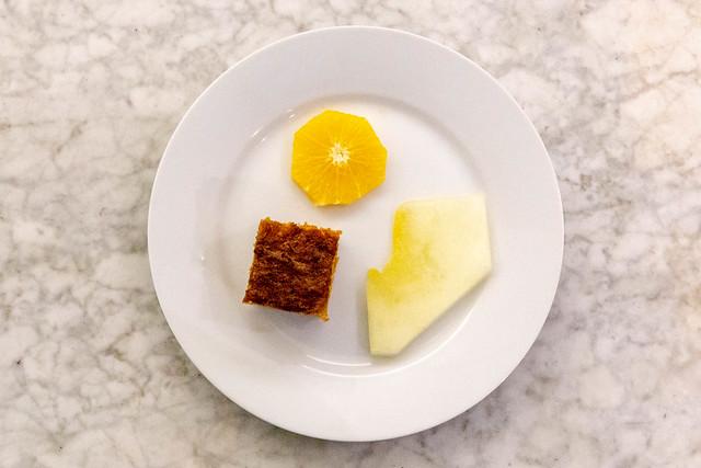 Aufsicht - Karottenkuchen auf weißem Teller mit einer Scheibe Orange und Honigmelone