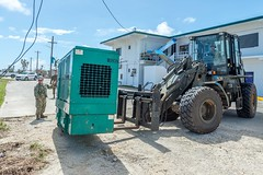 Sailors assigned to Naval Mobile Construction Battalion 1 place an emergency power generator at a de-energized location during recovery operations following Super Typhoon Yutu. (U.S. Navy/MCC Matthew R. White)