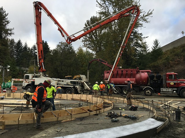 Workers pouring concrete on center island of Locust Way roundabout