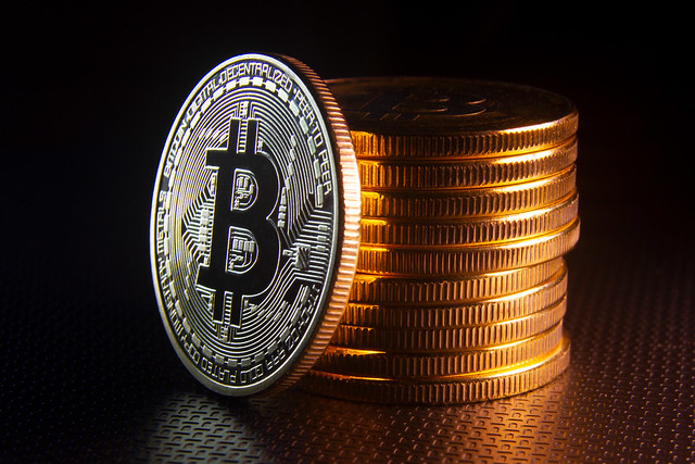 Bitcoin leaning against stack of Bitcoins