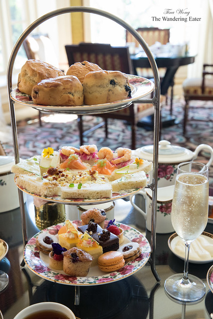 Glass of Champagne and tier of tea sandwiches and pastries