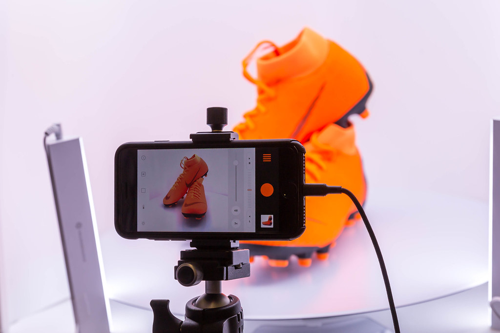 Creating product pictures of orange Nike football shoes with an Iphone on stative