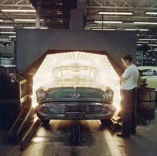 "An automobile exits a ""drying oven"" after being painted, General Motors, Oshawa, Ontario / Une automobile sortant du four de séchage après avoir été peinte, General Motors, Oshawa (Ontario)"