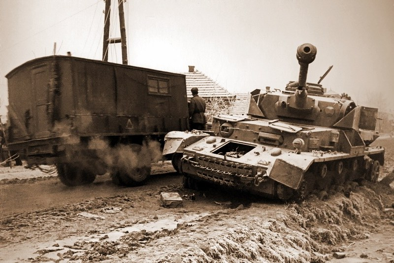 苏联卡车经过被殴打和遗弃在德国中型坦克Pz.Kpfw.IV的路边。