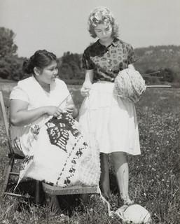 A woman knits a sweater as another woman holds the yarn, Koksilah, British Columbia /  Femme tricotant un chandail pendant qu'une autre tient la pelote, Koksilah (Colombie-Britannique)