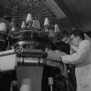 A student learns how to change a needle on a sweater-knitting machine, Quebec / Un élève apprend à insérer une aiguille dans une machine servant à tricoter des chandails (Québec)