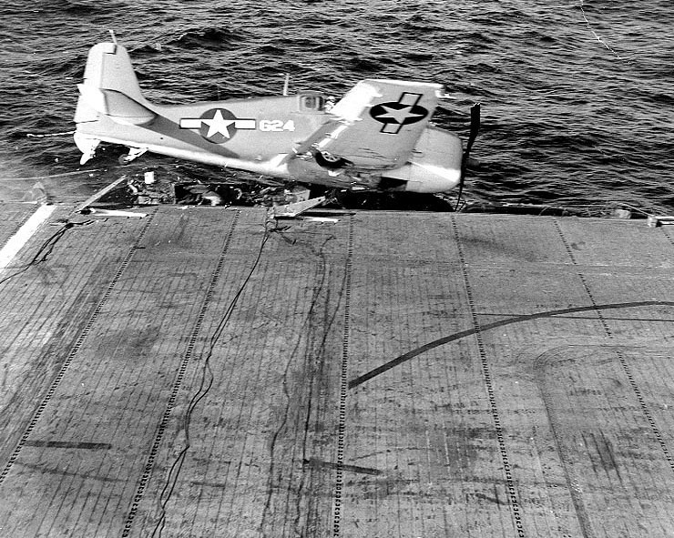 """A Grumman F6F-3 'Hellcat' fighter goes over the side of USS Barnes"