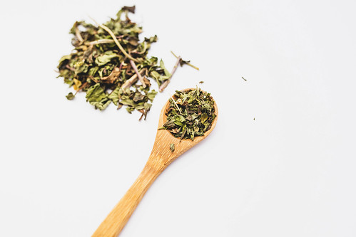 Peppemint loose leaf tea on a wooden spoon on white background | by wuestenigel