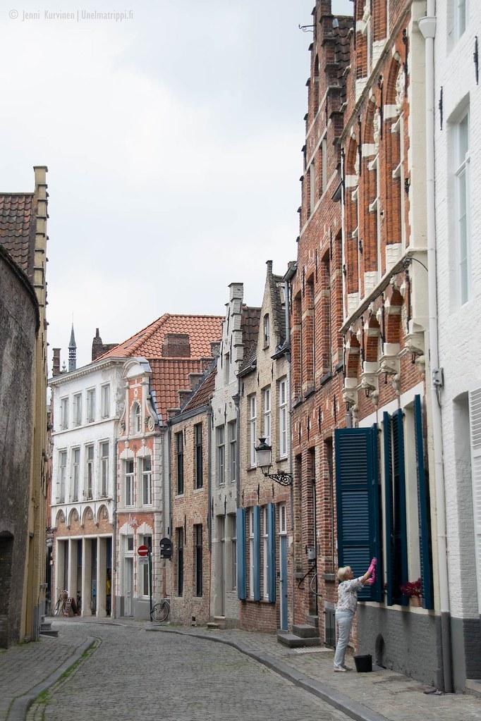 Nainen hiljaisella sivukujalla Bruggessa