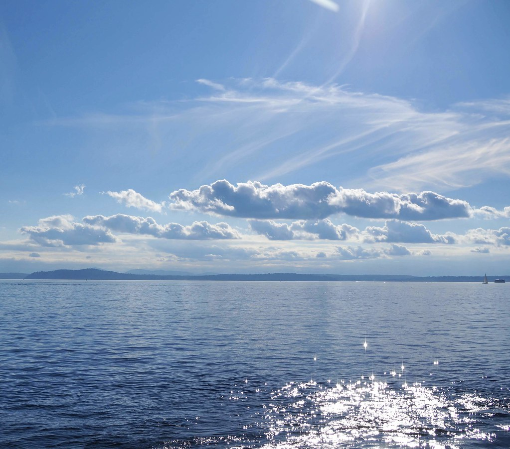 Blue ocean and sky with fluffy clouds