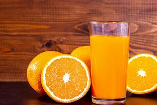 A glass of fresh orange juice with fruit oranges | by wuestenigel