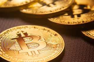 Bitcoin with row of Bitcoins   by QuoteInspector.com