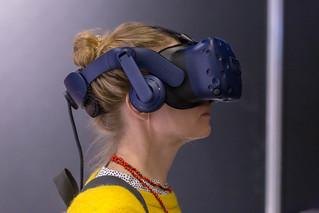 Dame mit gelbem Pullover testet die HTC Vive VR Brille an der Photokina in Köln | by verchmarco