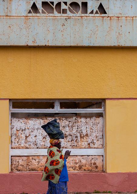 Angolan woman passing in front of a closed bank, Huambo Province, Vila Nova, Angola