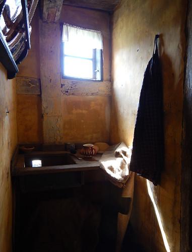 A tiny kitchen sink area lit by a single window in Den Gamle By, a recreated historic village in Aarhus, Denmark