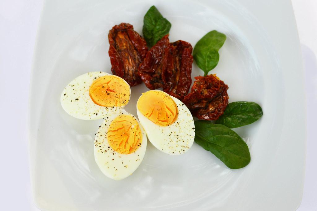 Uova sode tagliate con pomodorini secchi su un piatto