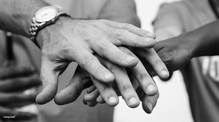 Team of business people stacking hands | by Rawpixel Ltd
