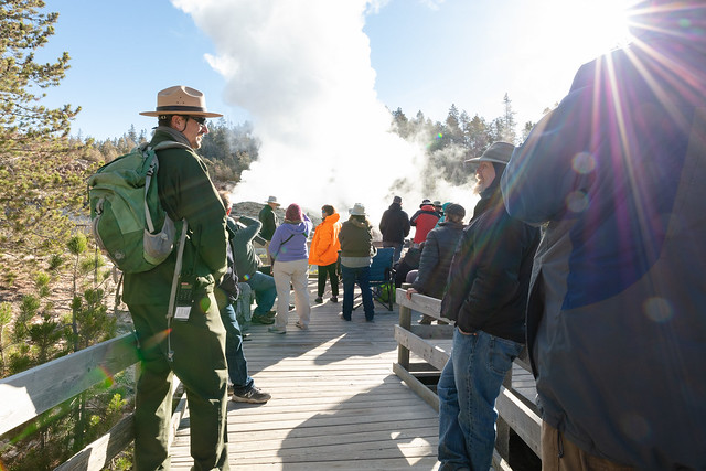 Ranger Mark Wolf chats with people at Steamboat Geyser minutes before an eruption
