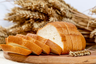 white bread sliced on a kitchen Board with wheat spikelets | by wuestenigel
