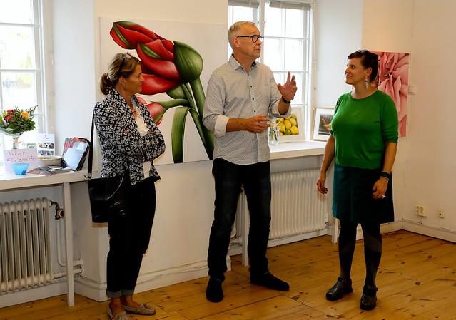 Söderköpings konstförenings ordförande Anders Svensson hälsar oktober månads utställare välkomna. T v. Eva Boström, t h Lovisa Lesse. I bakgrunden syns Eva Boströms färgsprakande tulpaner.
