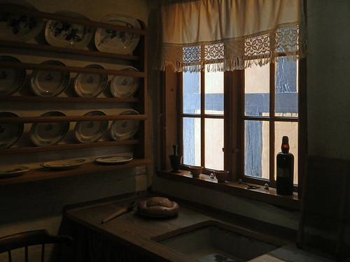 A larger kitchen lit by a single window in Den Gamle By, a recreated historic village in Aarhus, Denmark