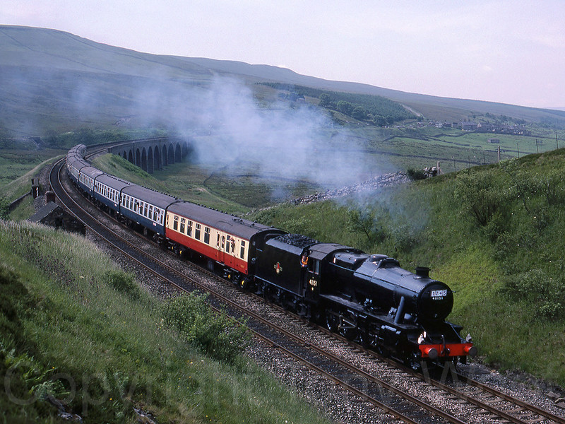 25th June 1988 LMF 8F 48151 has just crossed Dandry Mire viaduct and is about to enter Moorcock Tunnel accelerating away from a water stop at Garsdale