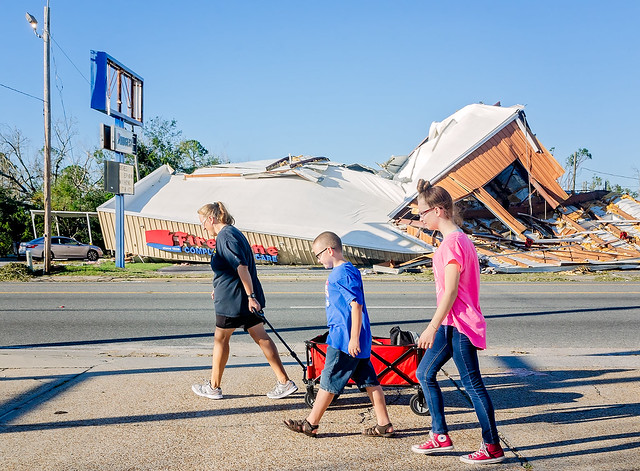 Family carries their belongings past building destroyed by Hurricane Michael in Panama City Florida