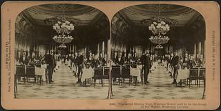 Dozens of waiters standing at two rows of tables with chandeliers overhead, Windsor Hotel, Montreal, Quebec / Des dizaines de serveurs debout près de deux rangées de tables avec un lustre suspendu au plafond, Hôtel Windsor, Montréal (Québec)