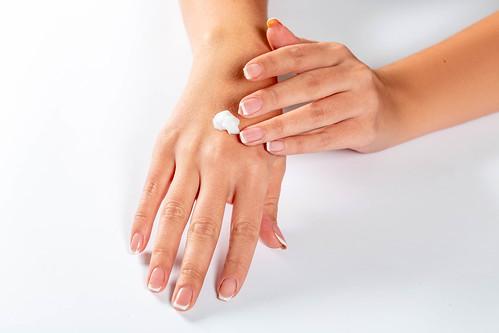 Girl spreads her hands with cream | by wuestenigel