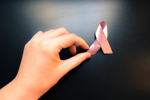 Female hand holding breast cancer awareness ribbon | by wuestenigel