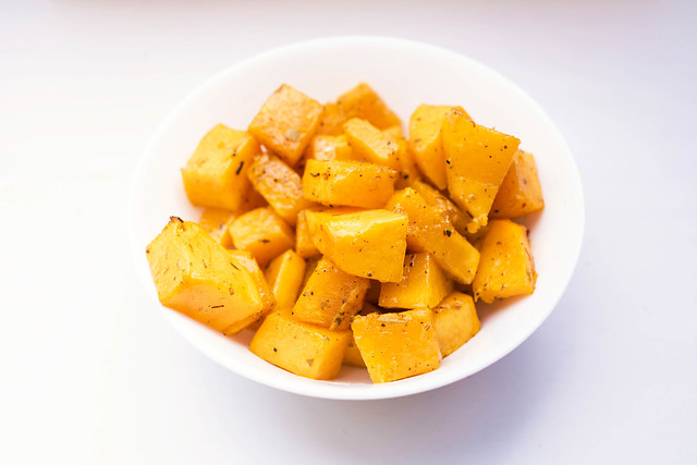 Roasted butternut squash with dried herbs in white bowl on white background