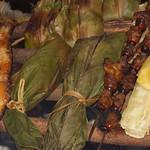 Fisch, gefüllte Palmenblätter, Käferlarven und Maniok auf dem Grill