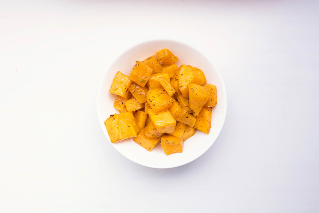 Top view of roasted butternut squash with dried herbs in a white bowl on white background