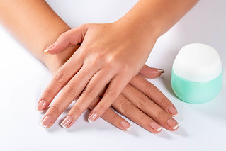 Beautiful woman hands with light manicure on nails and a jar of cream | by wuestenigel